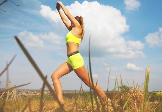 女性モデルが草原でトレーニングしている