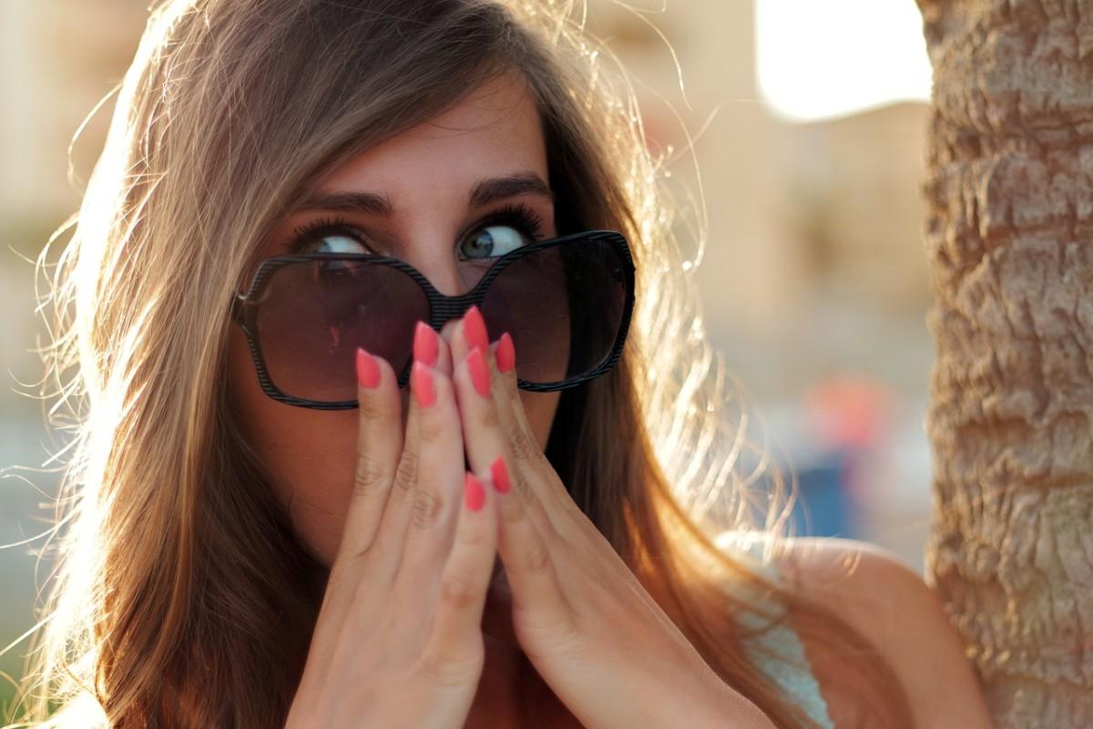 サングラスをした女性が驚いて両手で口に手を当てています