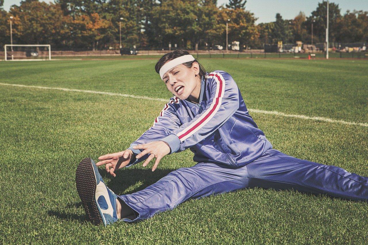 女性が芝生の上でストレッチ
