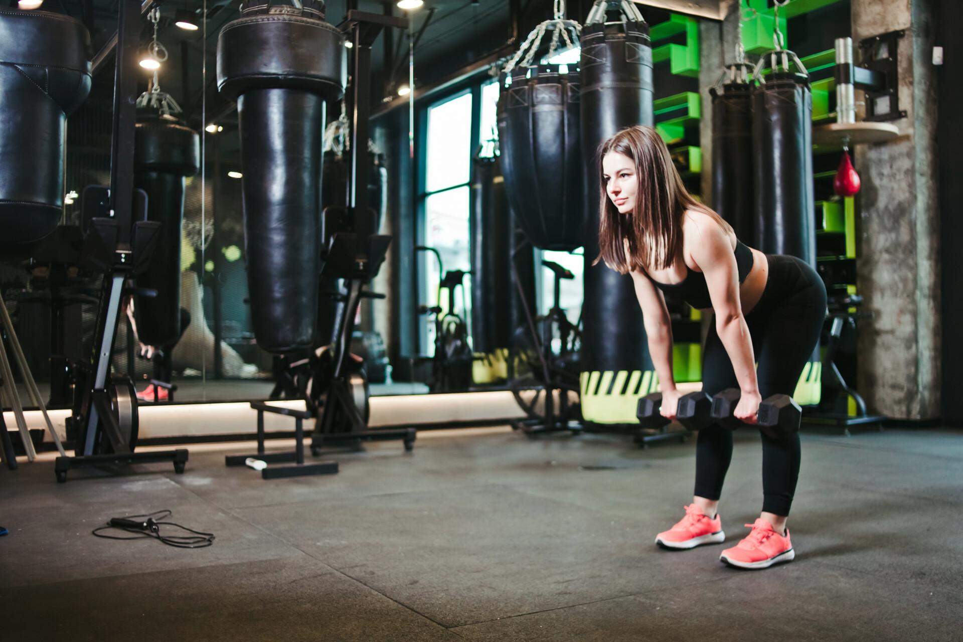 女性がダンベルで背中のトレーニングをしている