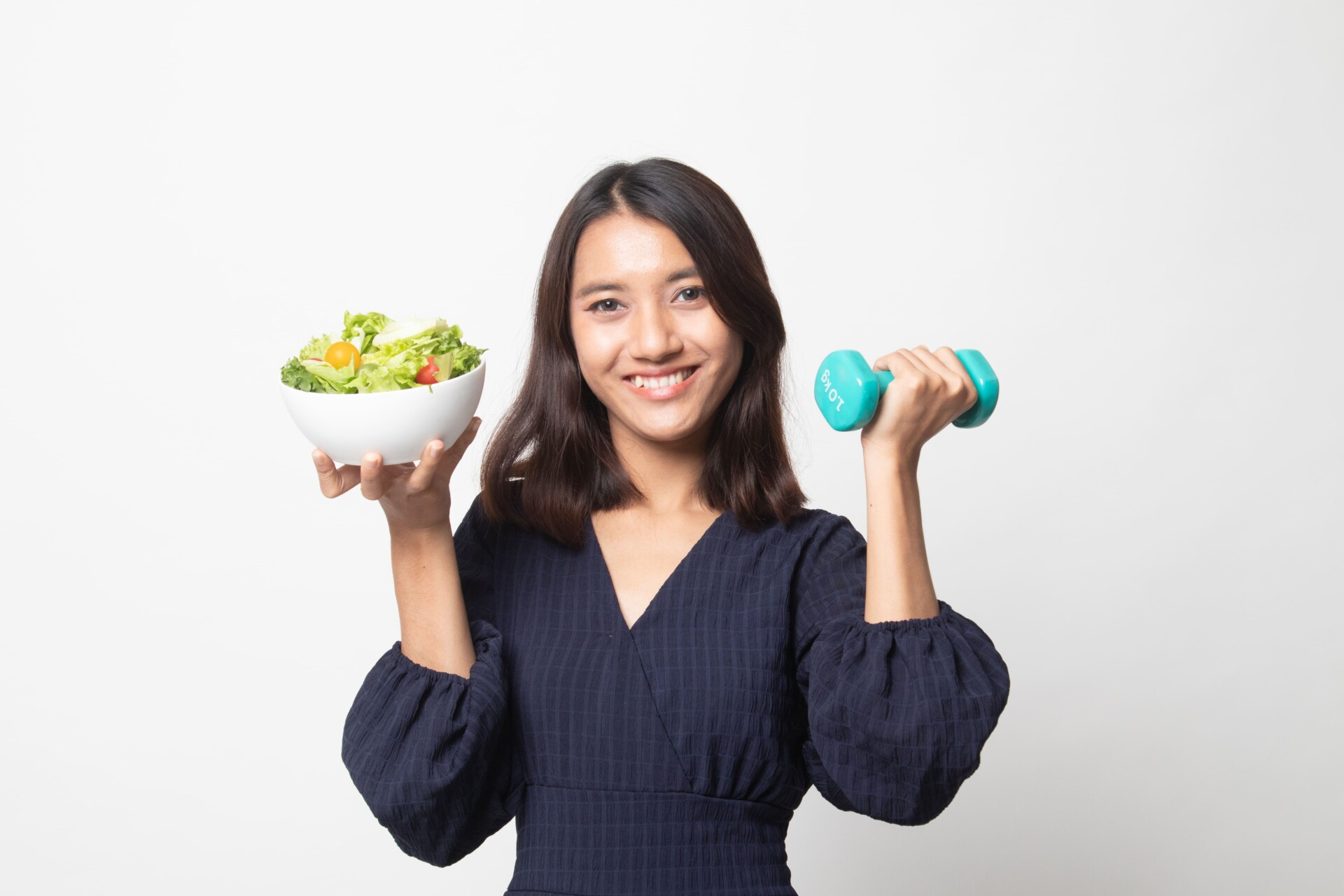 女性がダンベルと野菜を持っている