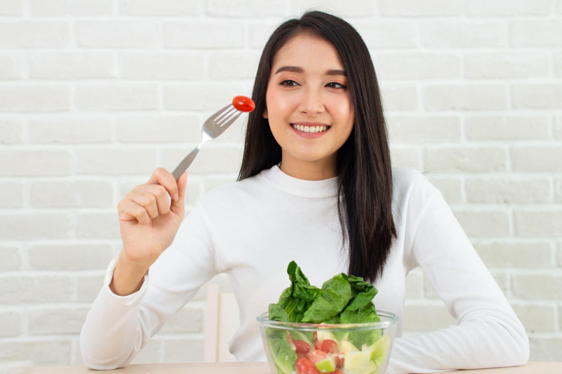 女性がトマトを食べようとしている写真