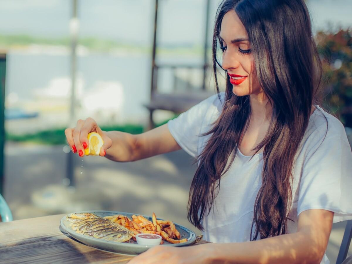 綺麗な女性が魚を食べようとしている写真